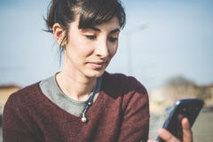 Giovane bella donna dei pantaloni a vita bassa che per mezzo dello Smart Phone Fotografia Stock
