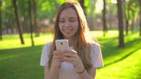 Giovane bella donna dei pantaloni a vita bassa che utilizza Smart Phone nella città stock footage