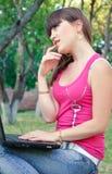 Giovane bella donna del brunette che per mezzo del suo taccuino Fotografia Stock Libera da Diritti