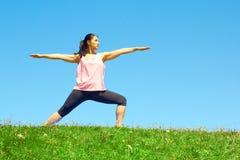 Giovane bella donna della corsa mista che fa posa del guerriero di yoga Fotografia Stock