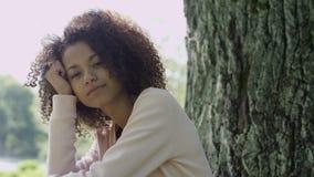 Giovane bella donna della corsa mista con i capelli ricci di afro che sorride felicemente in un parco verde archivi video