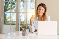 Giovane bella donna dello studente con il computer portatile alla tavola, a casa immagine stock