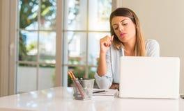 Giovane bella donna dello studente con il computer portatile alla tavola, a casa Immagini Stock