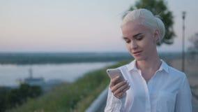 Giovane bella donna di affari che fa una telefonata all'aperto sul tramonto stock footage