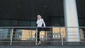 Giovane bella donna di affari che fa una telefonata fuori del centro di affari video d archivio
