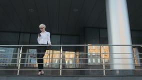 Giovane bella donna di affari che fa una telefonata fuori del centro di affari archivi video