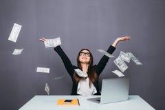 Giovane bella donna di affari che getta su soldi, sedentesi nel posto dell'ufficio con il computer portatile fotografie stock