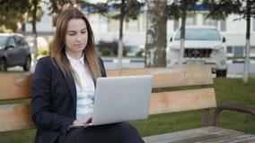 Giovane bella donna di affari che per mezzo del PC del computer portatile che si siede sul banco all'aperto archivi video