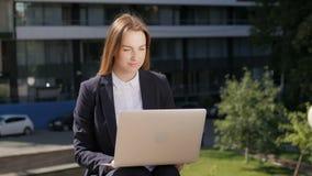 Giovane bella donna di affari che per mezzo del PC del computer portatile fuori del centro di affari archivi video