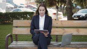 Giovane bella donna di affari che per mezzo del PC della compressa che si siede sul banco all'aperto archivi video