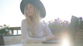 Giovane bella donna di affari che si siede ad una tavola con il computer portatile ed allo sguardo alla macchina fotografica video d archivio