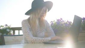 Giovane bella donna di affari che si siede ad una tavola con il computer portatile ed il sorriso video d archivio