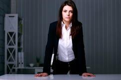 Giovane bella donna di affari che sta vicino alla tavola Fotografie Stock