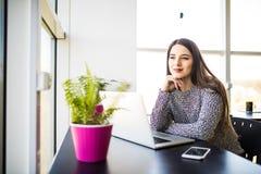 Giovane bella donna di affari pensierosa che lavora al computer portatile e che tiene mano sul mento mentre sedendosi al suo post Immagini Stock