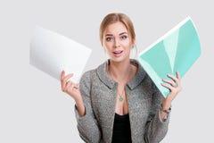 Giovane bella donna di affari in vestito nero, nella cartella della tenuta del rivestimento delle carte e di sorridere sul fondo  Immagini Stock