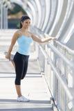 Giovane bella donna di sport atletico che allunga dopo il ponte moderno della città del metallo dell'incrocio corrente Fotografia Stock