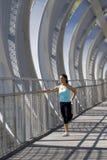 Giovane bella donna di sport atletico che allunga dopo il ponte moderno della città del metallo dell'incrocio corrente Immagine Stock Libera da Diritti