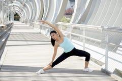 Giovane bella donna di sport atletico che allunga dopo il ponte moderno della città del metallo dell'incrocio corrente Fotografia Stock Libera da Diritti