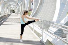 Giovane bella donna di sport atletico che allunga dopo il ponte moderno della città del metallo dell'incrocio corrente Fotografie Stock