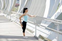 Giovane bella donna di sport atletico che allunga dopo il ponte moderno della città del metallo dell'incrocio corrente Immagine Stock