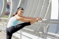 Giovane bella donna di sport atletico che allunga dopo il ponte moderno della città del metallo dell'incrocio corrente Immagini Stock Libere da Diritti