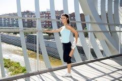 Giovane bella donna di sport atletico che allunga dopo il ponte moderno della città del metallo dell'incrocio corrente Immagini Stock