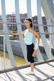 Giovane bella donna di sport atletico che allunga dopo il ponte moderno della città del metallo dell'incrocio corrente Fotografie Stock Libere da Diritti