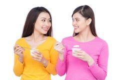 Giovane bella donna due che mangia yogurt come la prima colazione o spuntino Isolato su bianco Fotografie Stock Libere da Diritti