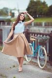 Giovane bella, donna elegante vestita con la bicicletta Fotografia Stock