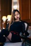 Giovane bella donna elegante in vestito di seta splendido che si siede dentro Immagini Stock