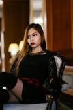 Giovane bella donna elegante in vestito di seta splendido che si siede dentro Fotografia Stock
