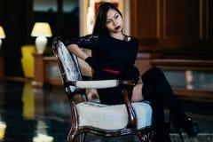 Giovane bella donna elegante in vestito di seta splendido che si siede dentro Immagine Stock