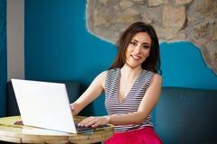 Giovane bella donna felice che per mezzo del computer portatile Fotografie Stock Libere da Diritti