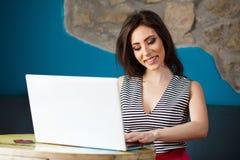 Giovane bella donna felice che per mezzo del computer portatile Fotografie Stock