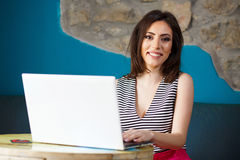 Giovane bella donna felice che per mezzo del computer portatile Fotografia Stock Libera da Diritti