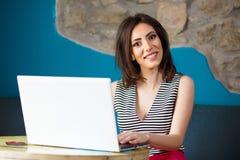 Giovane bella donna felice che per mezzo del computer portatile Immagini Stock