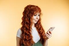 Giovane bella donna felice che per mezzo dello Smart Phone fotografia stock libera da diritti