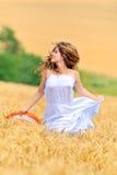 Giovane bella donna nel campo di frumento dorato Immagini Stock