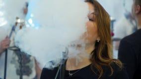 Giovane, bella donna nel fumo della barra o del night-club un narghilé o uno shisha Il piacere di fumo stock footage