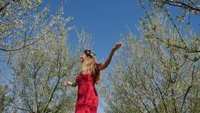 Giovane bella donna nella condizione lunga del vestito nel giardino del fiore di primavera archivi video