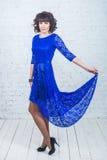 Giovane bella donna nella parte anteriore stante del vestito blu del muro di mattoni di bianco del fondo Fotografia Stock