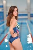 Giovane bella donna sexy che sta vicino all'acqua blu della piscina immagini stock