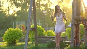 Giovane bella donna sorridente che ondeggia sull'oscillazione in natura verde del parco di estate Ragazza graziosa in vestito bia archivi video