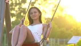 Giovane bella donna sorridente che ondeggia sull'oscillazione in natura verde del parco di estate Ragazza graziosa in vestito bia video d archivio