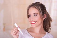 Giovane bella donna sorridente che tiene un tampone del cotone di mestruazione in sua mano, in un fondo vago immagini stock libere da diritti