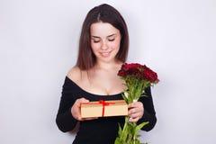 Giovane bella donna sorridente con i fiori ed il regalo Datazione, rel fotografie stock