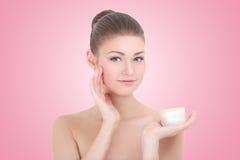 Giovane bella donna sorridente con la bottiglia crema sopra il rosa Fotografia Stock