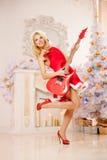 Giovane bella donna sorridente di Santa vicino all'albero di Natale con Immagini Stock
