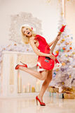 Giovane bella donna sorridente di Santa vicino all'albero di Natale con Immagine Stock