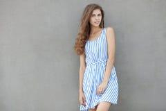 Giovane bella donna sorridente felice in vestito leggero con capelli ricci castana lunghi che posano contro la parete su un caldo Fotografia Stock Libera da Diritti